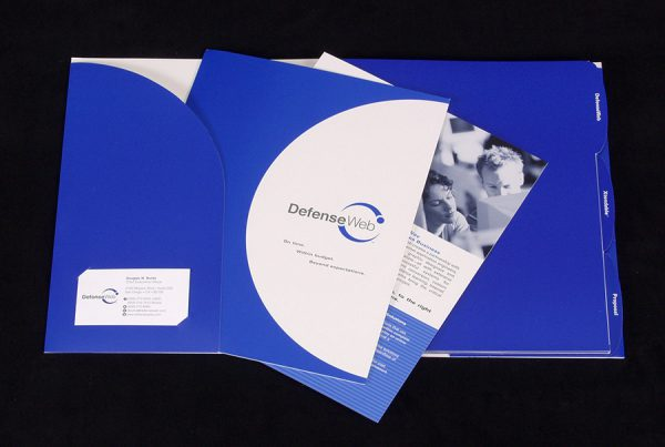 DefenseWeb catalog design photo wit blue catalog and pockets shown