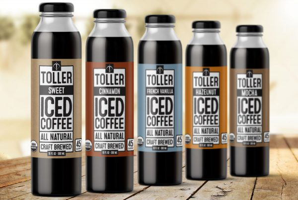 packaging design portfolio example of 5 coffee bottles with colored labels on wooden table
