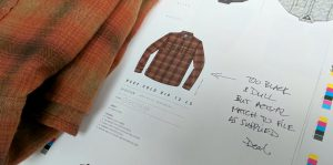 Closeup photo of catalog photo of woven shirt with real shirt next to it, and note explaining the two don't match