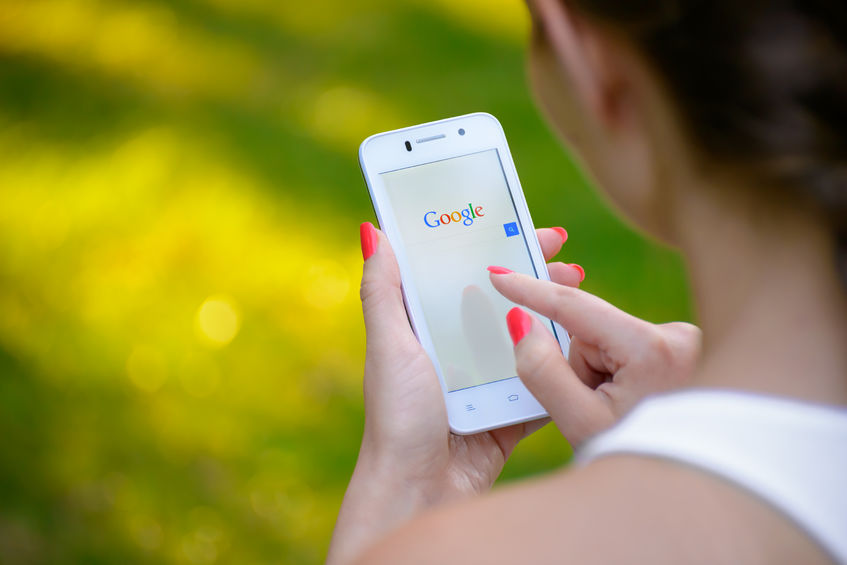 Woman holding smartphone with Google search page visible