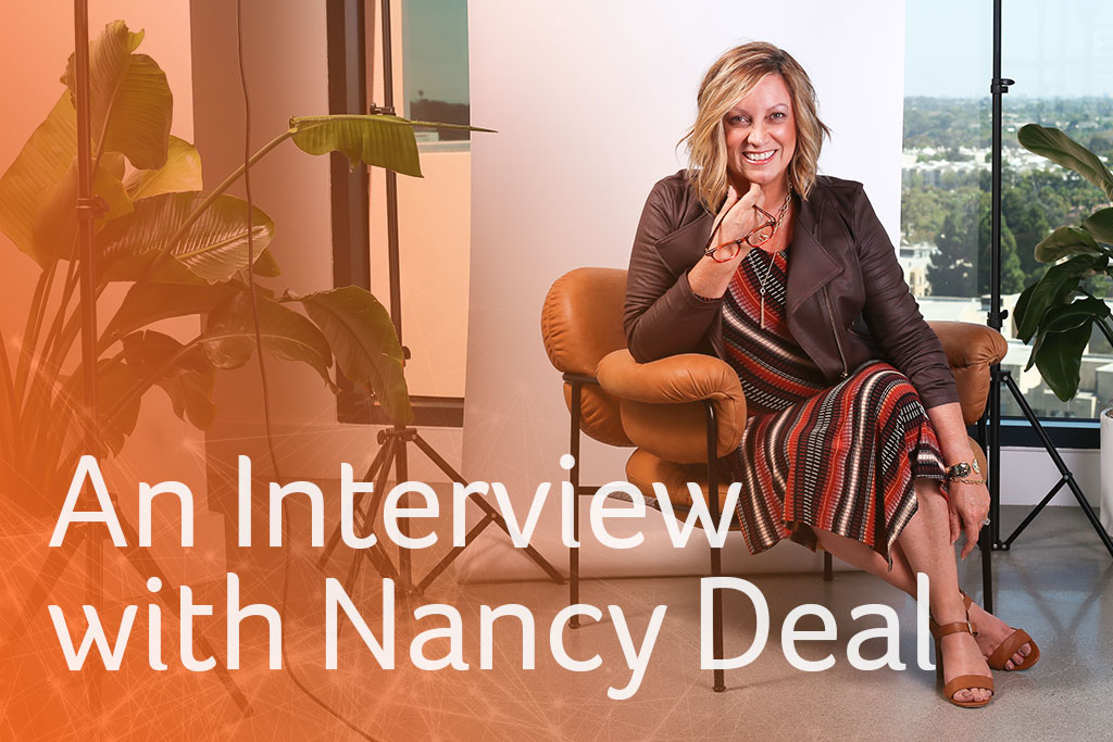 An interview with Nancy Deal, designer woman sitting and smiling intently at camera