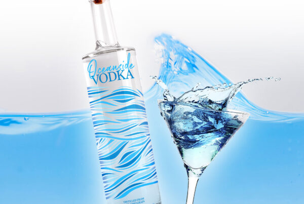 Packaging design of a vodka bottle with martini glass and water splashing in the background